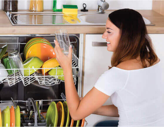 brita pro softeners filters woman looking at clean dishes in dishwasher